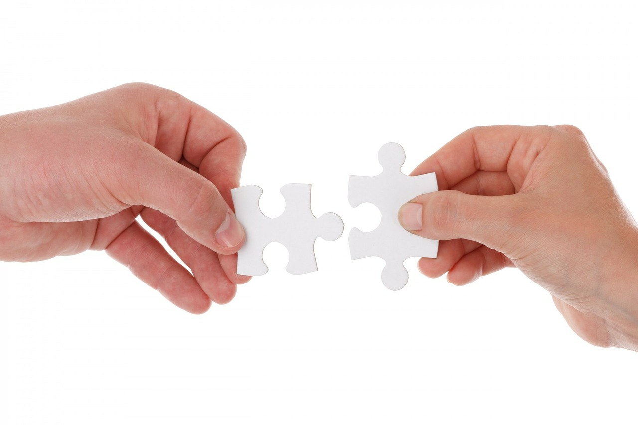 two hands from two persons solve the puzzle together collaboratively.